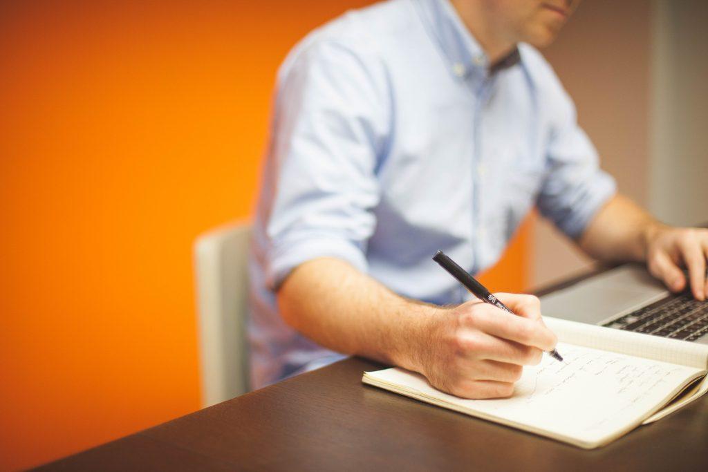 Foto mit lernendem Mitarbeiter am Laptop, der sich Notizen macht